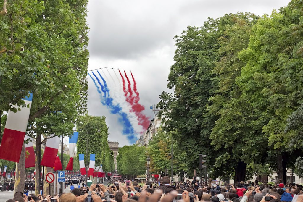 PARIS - JULY 14: People are watching French Patrouille de France at a military parade in the Republic Day (Bastille Day) on Champs Elysees in Paris, France on July 14, 2012.